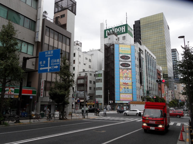 Street with sign saying Akihabara is ahead and a manga style advertisement a bit further back